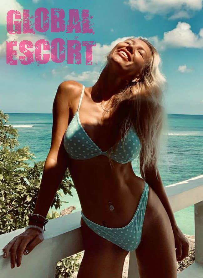 Elite European escort blonde in a blue sexy swimsuit on the sea