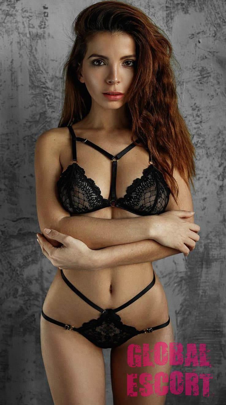 Half-naked sexy escort model Karina stands in black transparent lingerie