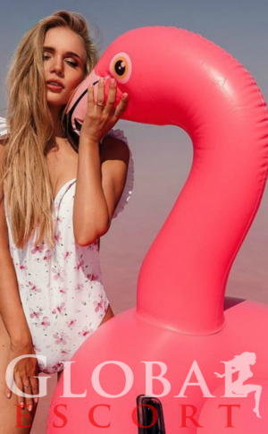 Sexy Model in a white swimsuit with a pink flamingo