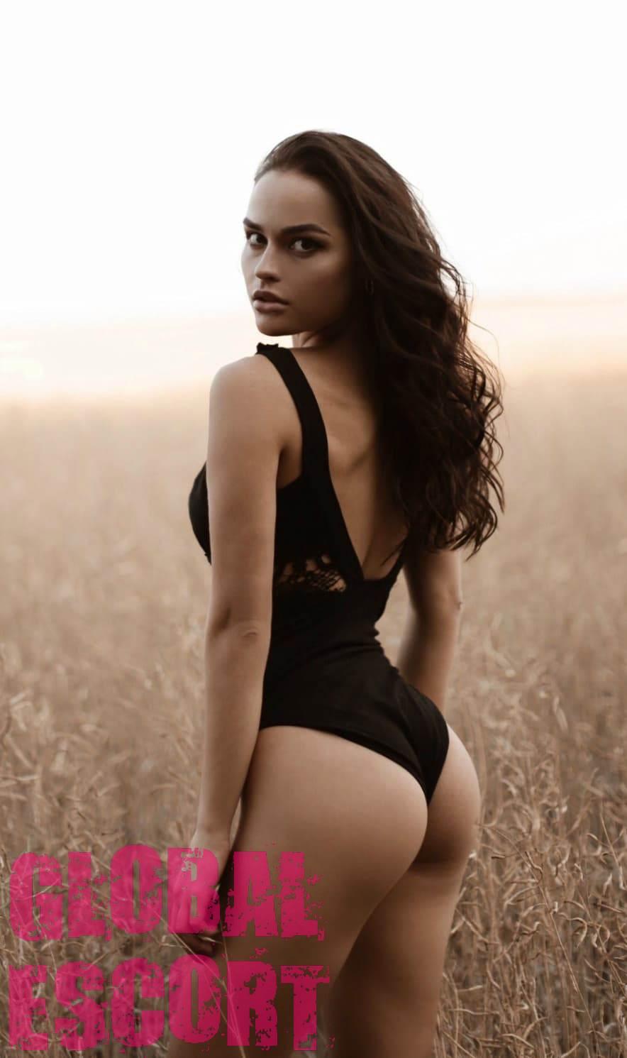 Sexy brunette Sofia in a black swimsuit in a field