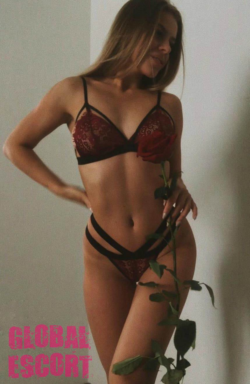 beautiful escort model in a transparent burgundy swimsuit holds a rose