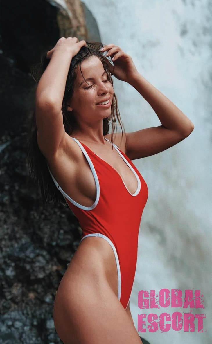 beautiful escort model posing in a red swimsuit near a waterfall