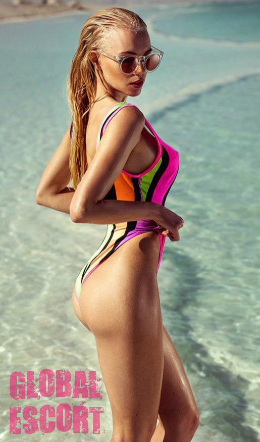 beautiful young escort blonde in a multi-colored swimsuit posing with glasses in the sea