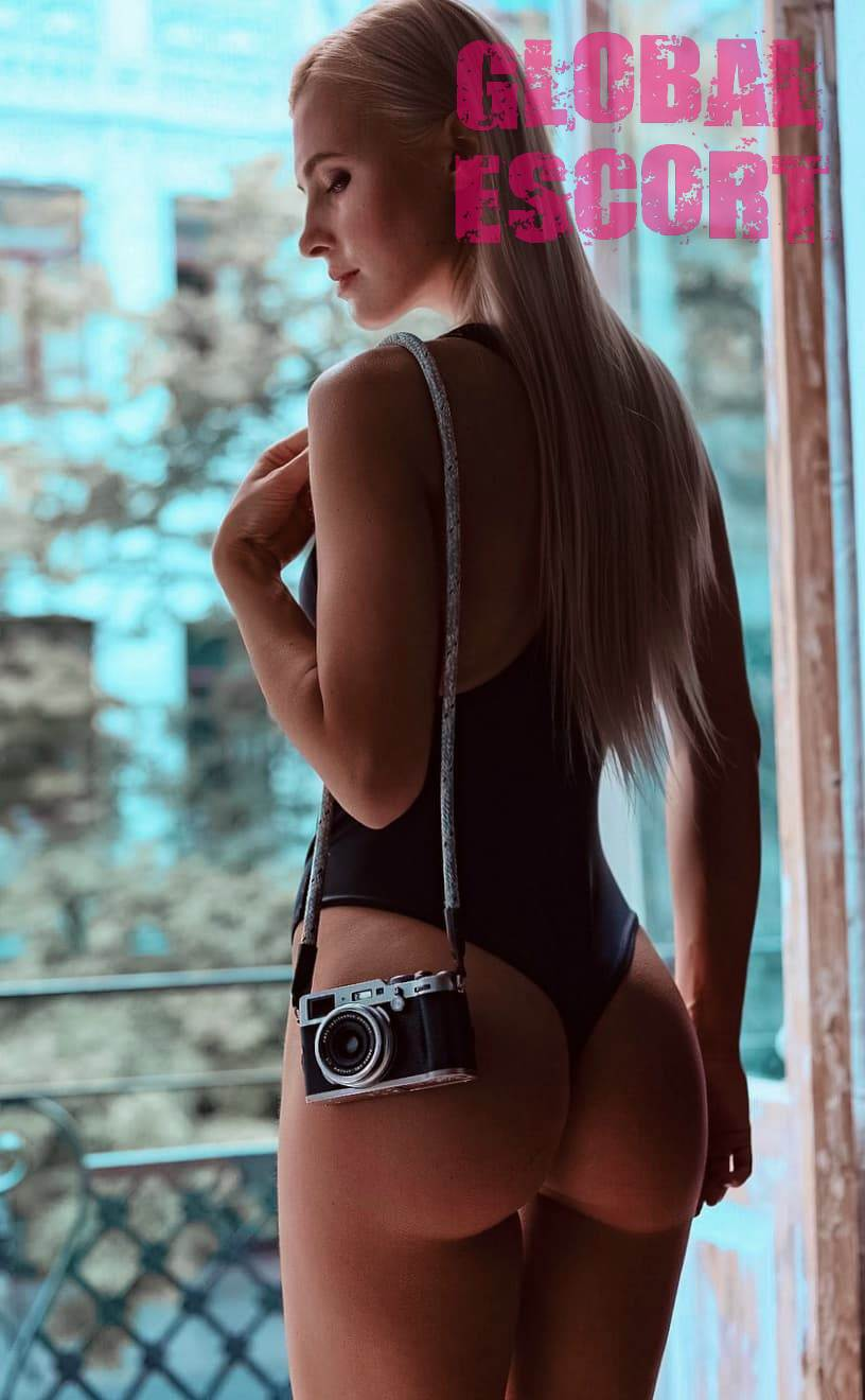 charming Ukrainian blonde in a black swimsuit near the window with a camera on the ass