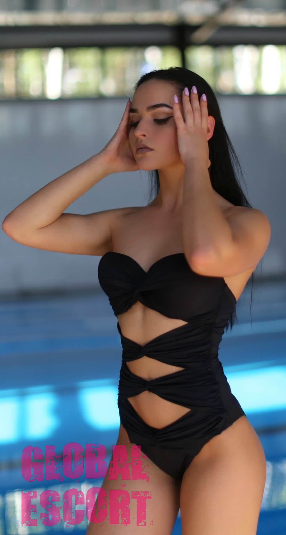 charming brunette in a black bathing suit at a photo session on the background of the pool