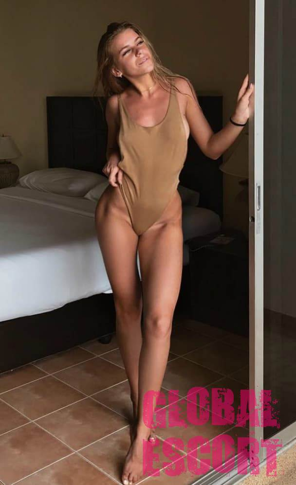 charming escort model in a beige swimsuit in a hotel room