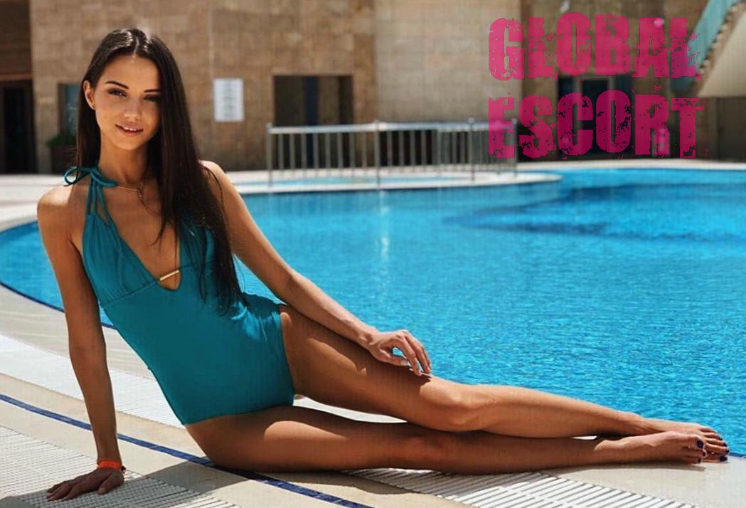 charming escort model in a blue swimsuit lies near the pool