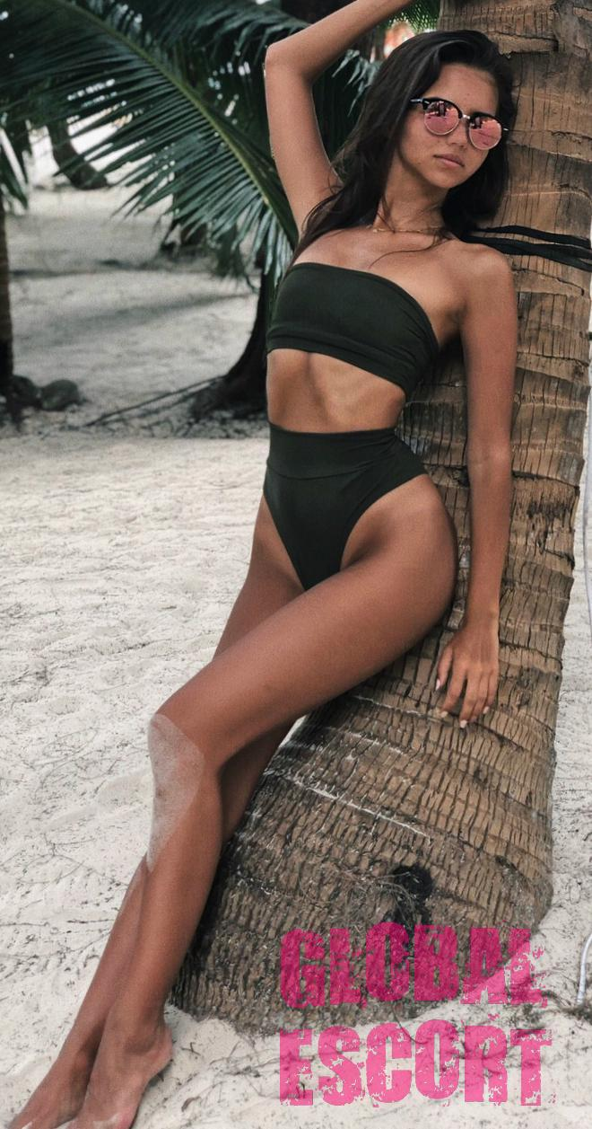 charming escort model in a green bathing suit posing on the beach near the tree in glasses