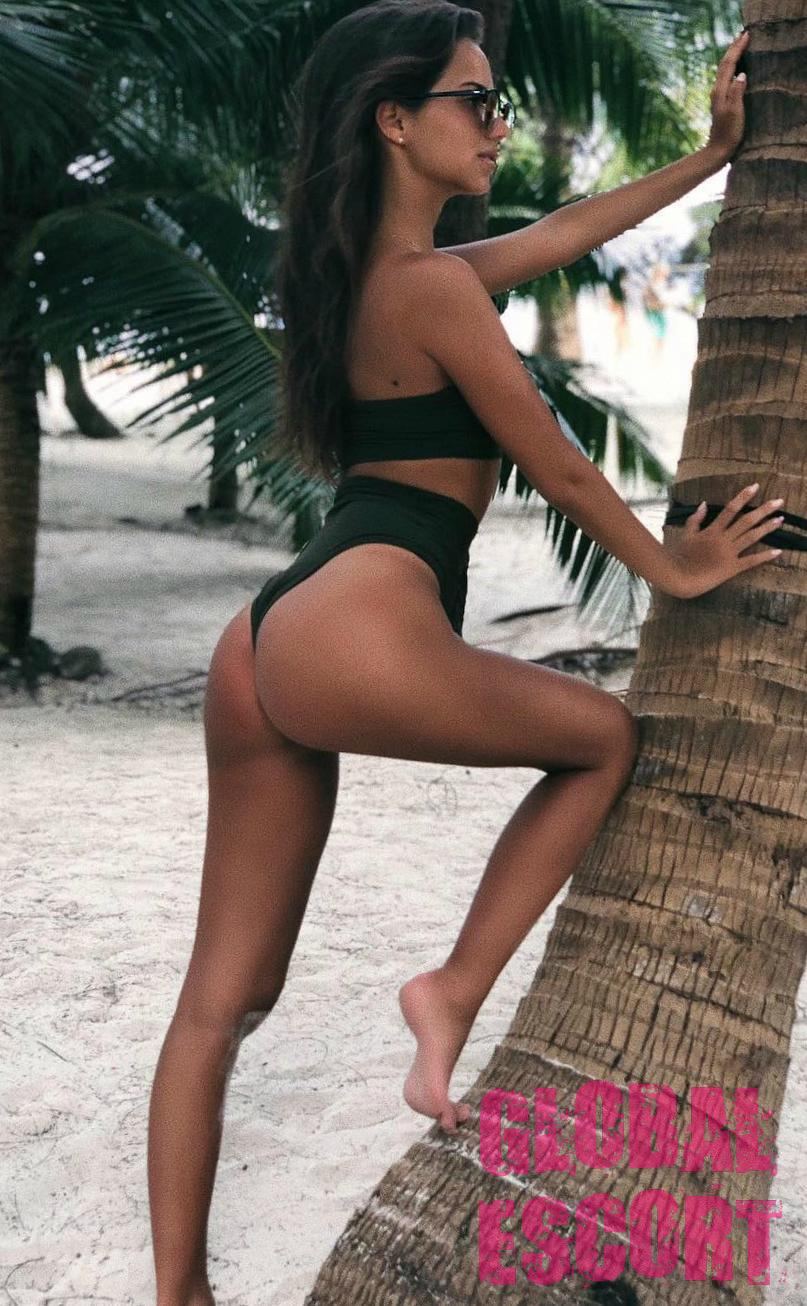 charming escort model in a green swimsuit posing on the beach near a tree