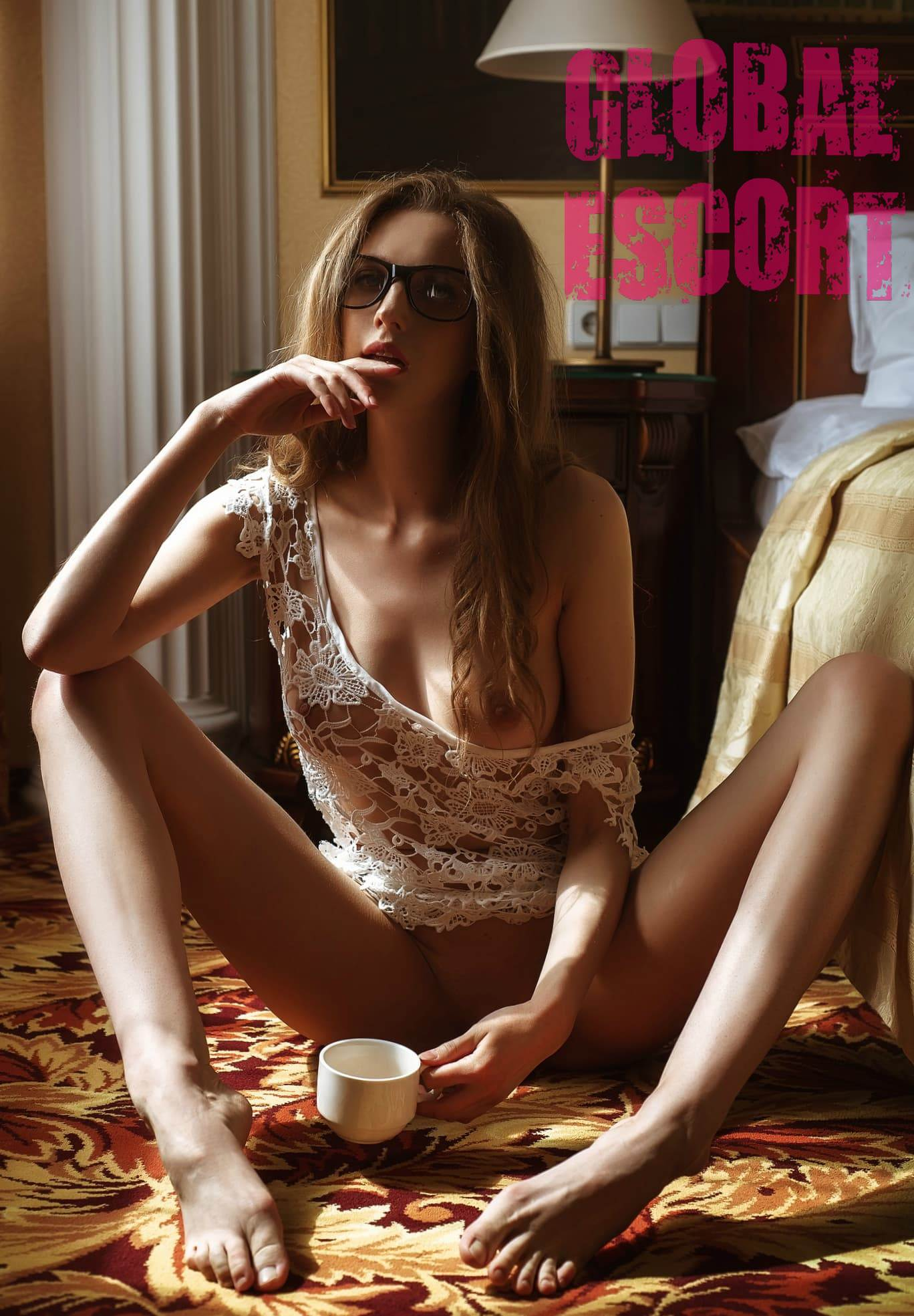 half-naked Ukrainian model sits on the floor in a room in white transparent linen and drinks coffee