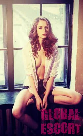 half-naked Ukrainian sexy escort model sitting near the window