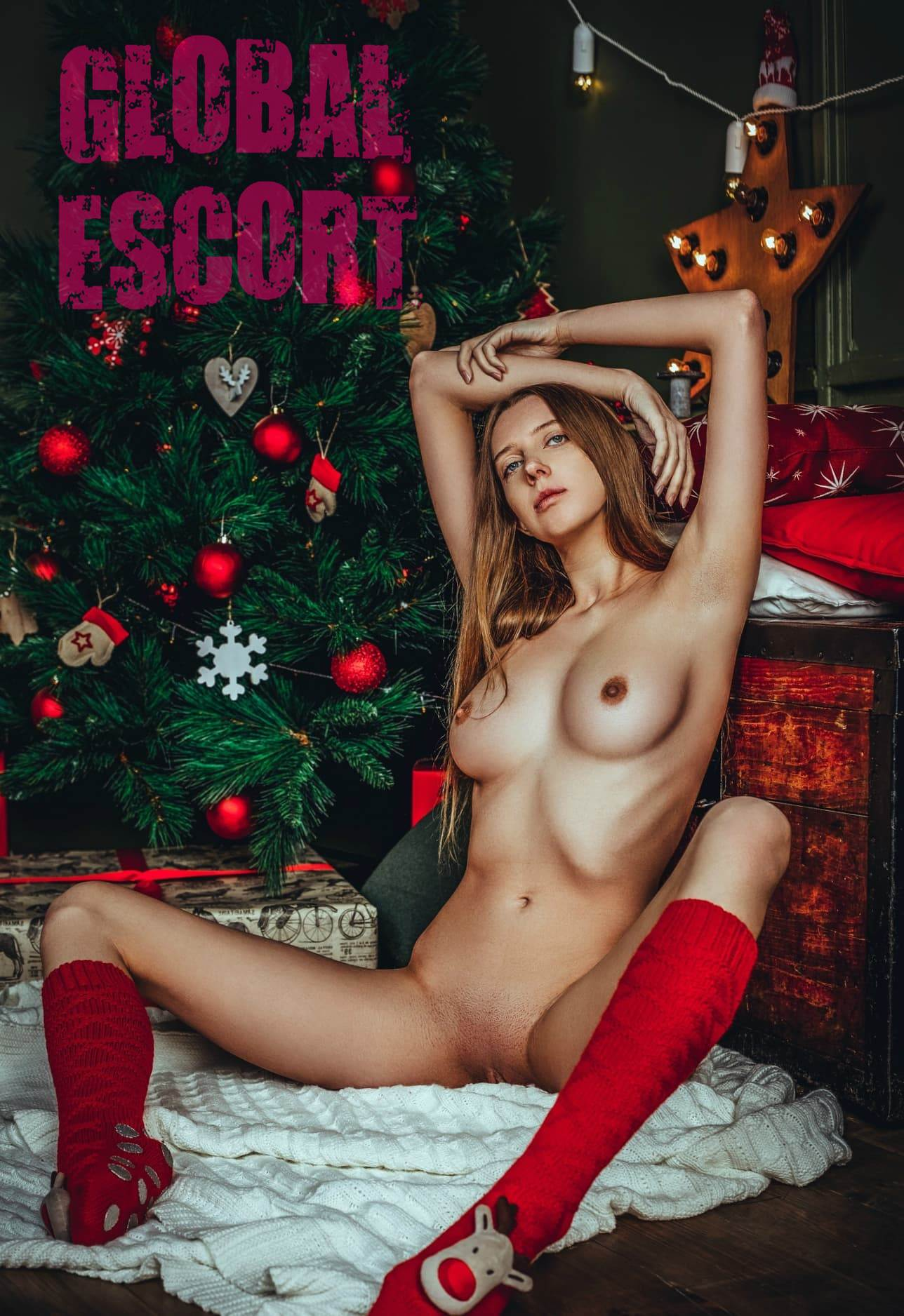 naked escort model sits near a Christmas tree and spreads her legs on a white carpet
