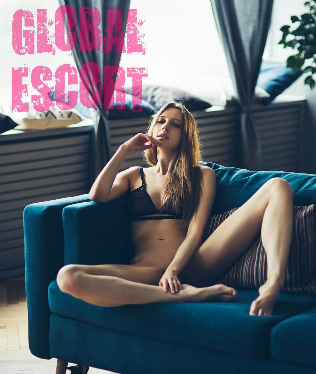 naked escort model sits on a blue sofa in the room and spreads her legs
