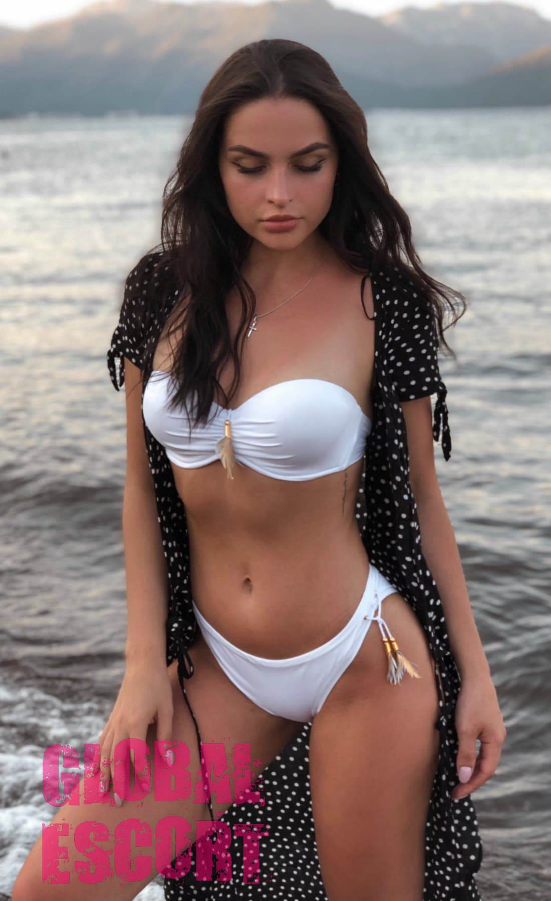 sexy brunette in a white swimsuit on the sea