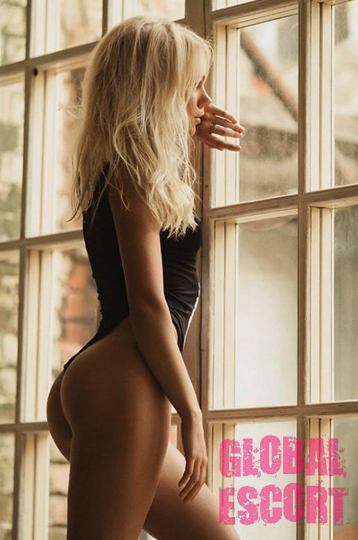 sexy escort model Dasha in a black bathing suit at a photo shoot near the window