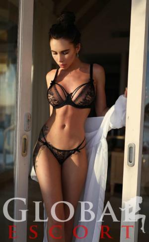 sexy escort model Polina in black lingerie on the balcony