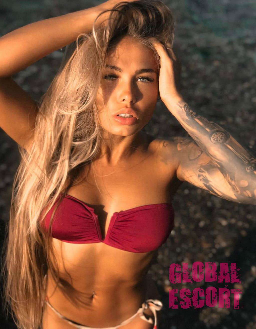 sexy escort model Valeria in a red swimsuit and a tattoo on her arm
