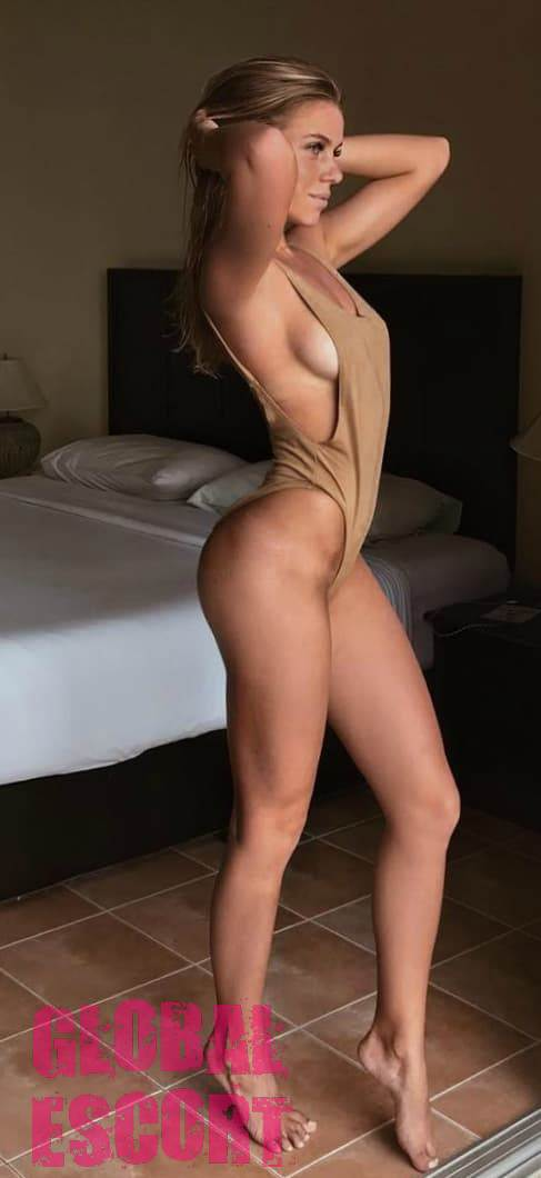 sexy escort model in a beige swimsuit in a hotel room