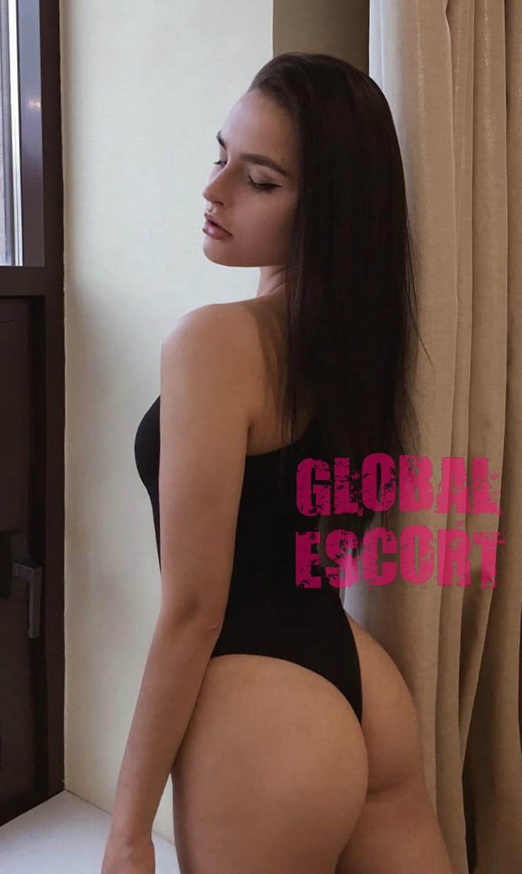 sexy escort model in a black swimsuit near the window