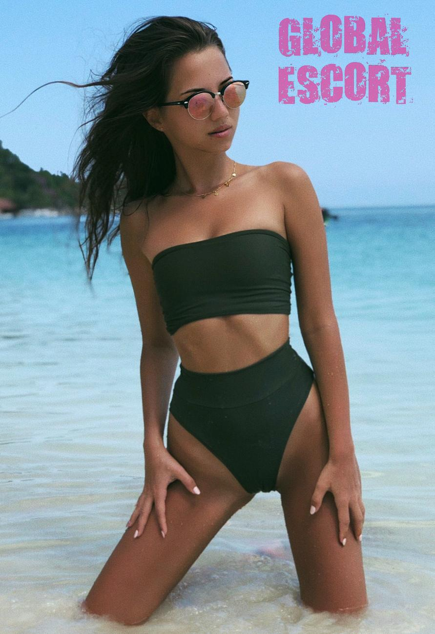 sexy escort model in a green swimsuit and glasses kneeling in the sea