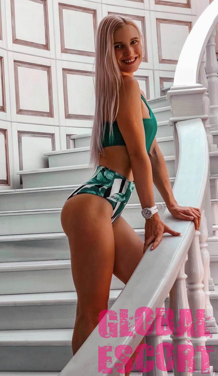 sexy escort model stands on the white steps in a green swimsuit
