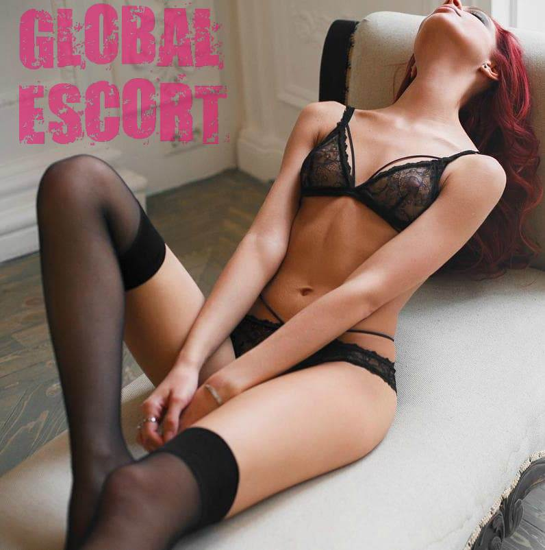 sexy red-haired escort model lies in transparent black lingerie on the armchair
