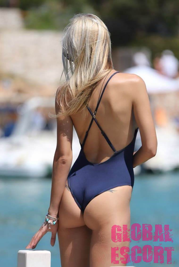 tanned blonde in a blue sexy swimsuit on the pier