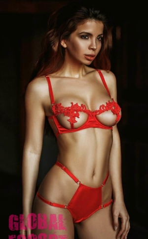 tender escort model posing in transparent red lingerie in a black room