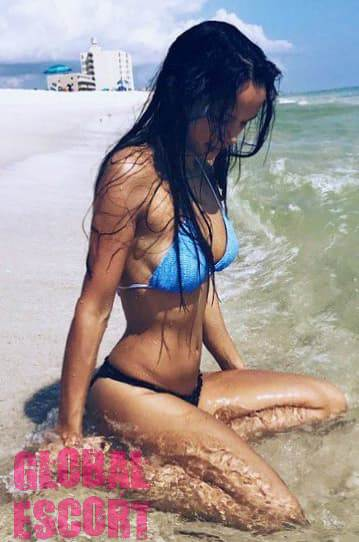 wet sexy brunette in a blue swimsuit sitting on the beach