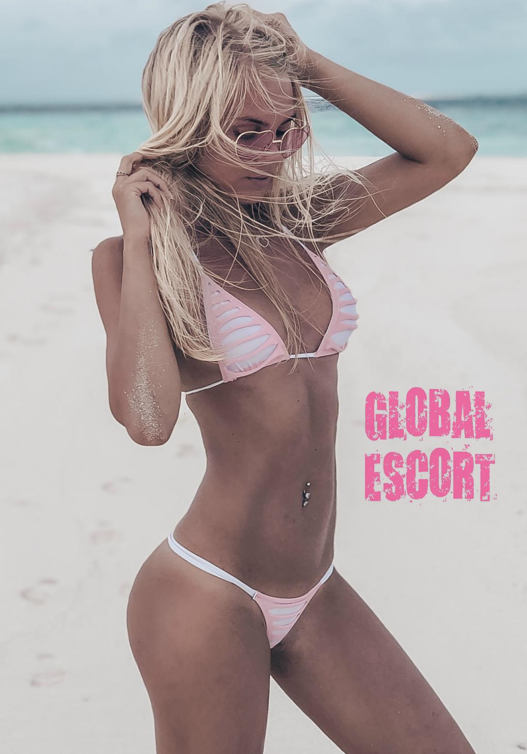 young escort model Dasha in a pink swimsuit posing on the beach