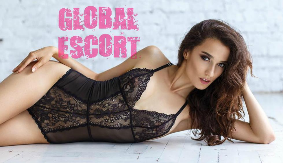 beautiful escort model Sofia in beige lingerie sitting in a room on a white bed